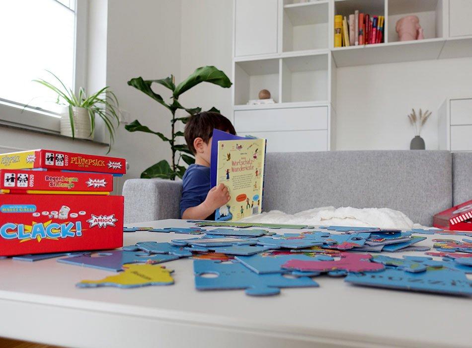 Krankes Kind liegt auf der Couch und liest ein Buch